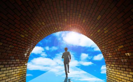 青空に向かって歩いているビジネスマン