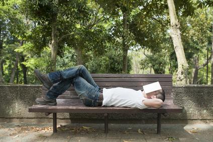 公園のベンチで昼寝をする男性